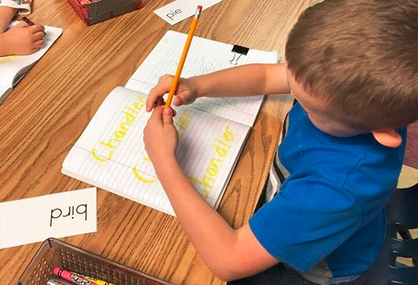 A preschool kid boy wearing blue shirt writing his name on a notebook at a Christian Preschool & Daycare Serving Loganville, GA