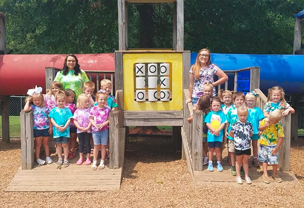 preschoolers grouping into two with the happy teacher in the playground for their enrichment activity at a Christian Preschool & Daycare Serving Loganville, GA