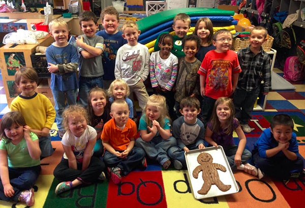 Happy diverse group of preschoolers gathering around showing a huge gingerbread cookie at a Christian Preschool & Daycare Serving Loganville, GA
