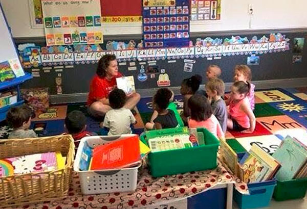Group of preschool kids gather arounfdto listen to teacher reading them a story at a Christian Preschool & Daycare Serving Loganville, GA