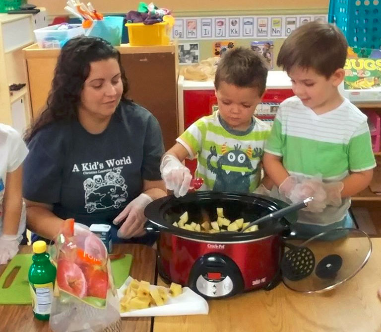 Preschool kids with teacher carefully putting some spices on the vegetable they are cooking on an electric pot at a Christian Preschool & Daycare Serving Loganville, GA