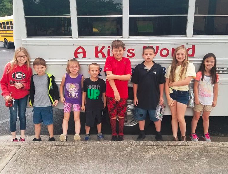 Group of diverse kids beside their school bus at a Christian Preschool & Daycare Serving Loganville, GA