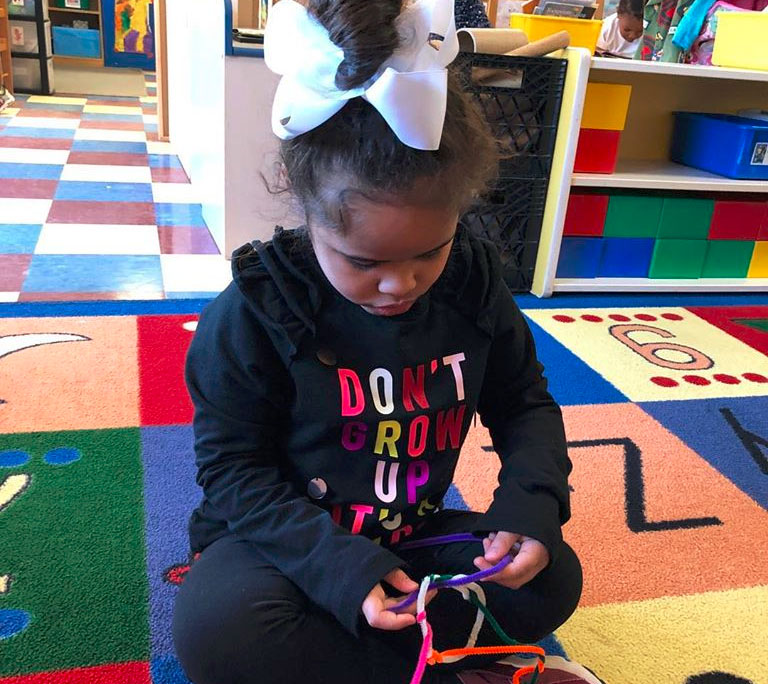 An african american young little girl trying to design a ring using colorful strings at a Christian Preschool & Daycare Serving Loganville, GA