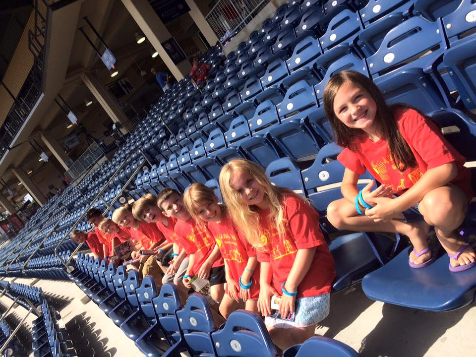 Group of young kids enjoying at the stadium wearing red school themed shirt at a Christian Preschool & Daycare Serving Loganville, GA