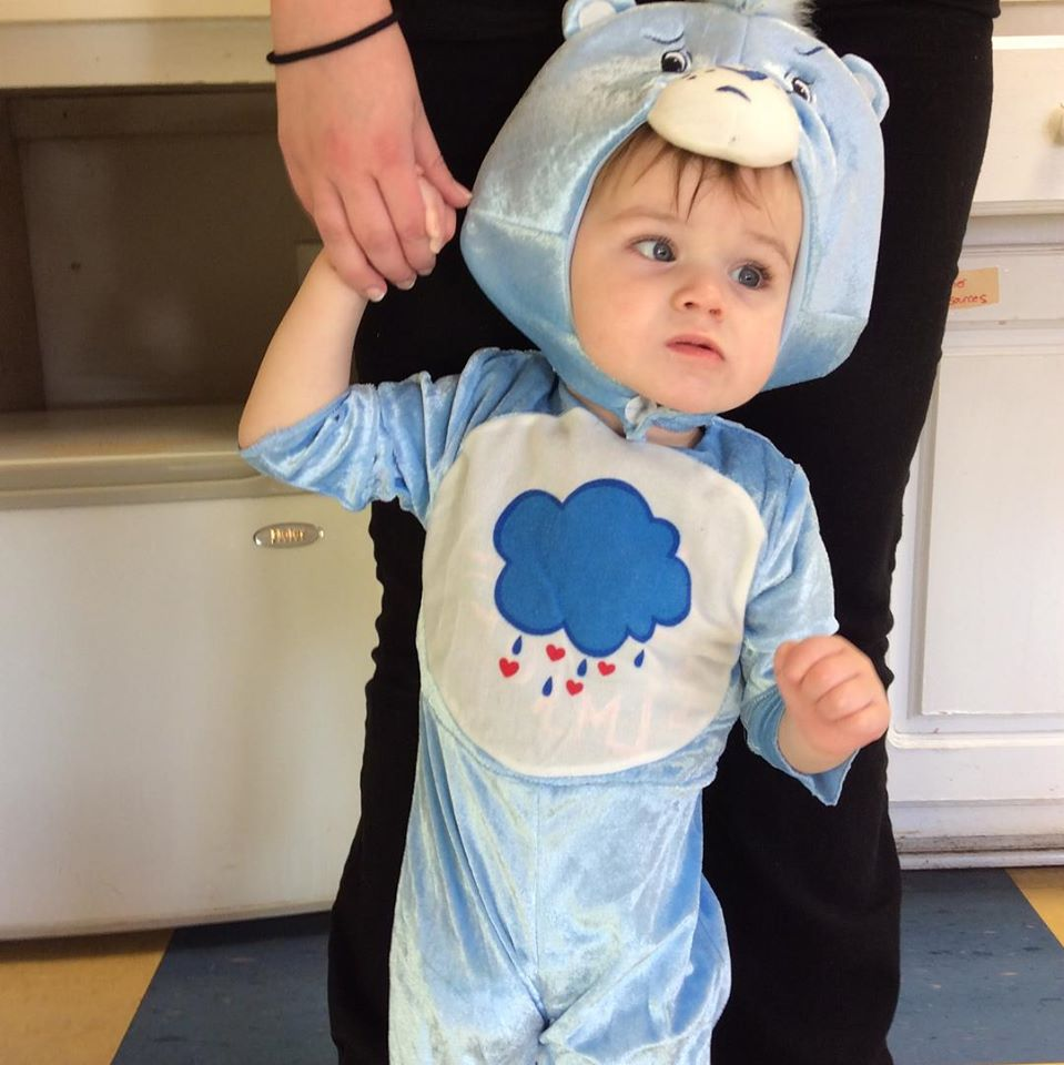 Little toddler boy wearing a blue care bear costume holding mommy's hand at a Christian Preschool & Daycare Serving Loganville, GA