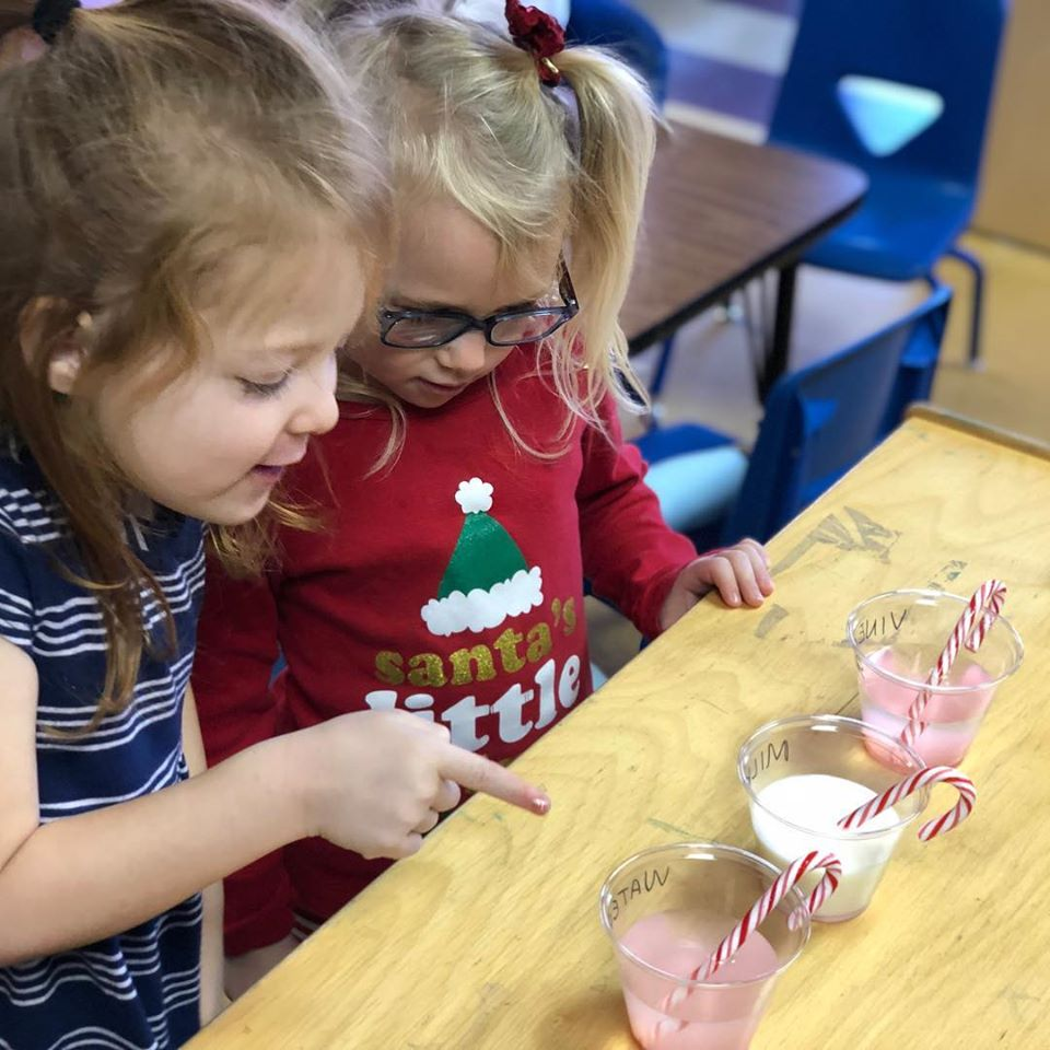 Two little girls choosing from a 3 cups of fruit shake with a candy cane on top at a Christian Preschool & Daycare Serving Loganville, GA