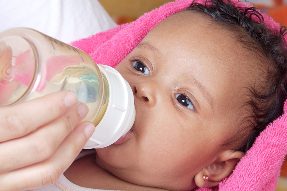 Adorable baby drinking a bottle - focus in the face at a Christian Preschool & Daycare Serving Loganville, GA