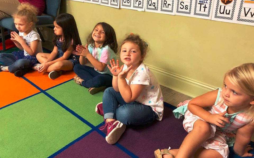 Group of little girls sitting on the floor having fun with their group activity at a Christian Preschool & Daycare Serving Loganville, GA