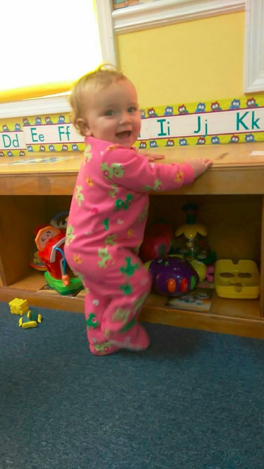 Smiling cute little baby wearing pink pajamas at a Christian Preschool & Daycare Serving Loganville, GA