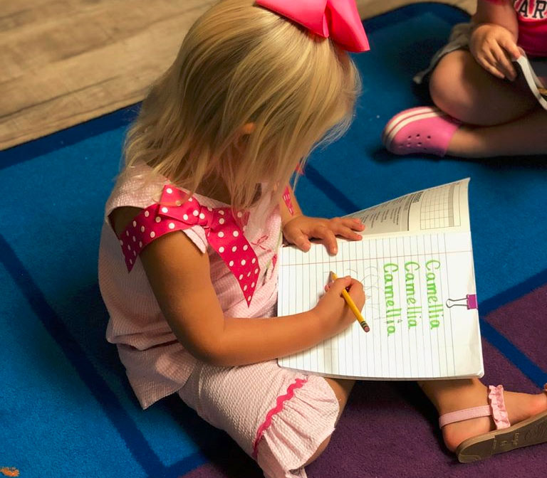 Little girl wearing pink dress Copying and trying to write her name on a notebook with her name on it at a Christian Preschool & Daycare Serving Loganville, GA