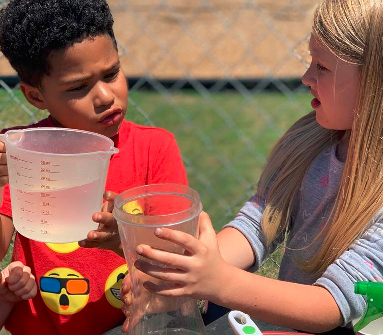 A preschool boy and a girl teaming up to pour water into a plastic tube at a Christian Preschool & Daycare Serving Loganville, GA