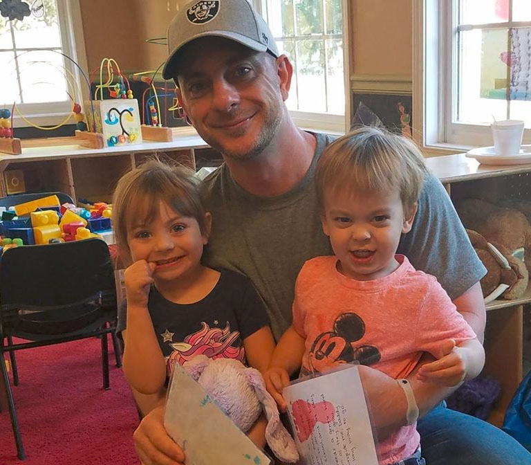 Happy Daddy and two little kiddos each wearing a Disney inspired shirt at a Christian Preschool & Daycare Serving Loganville, GA