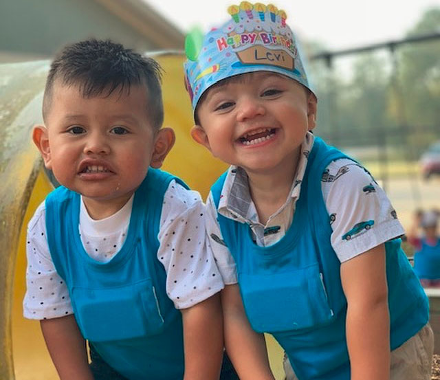 Happy little nursery boys enjoying birthday celebration wearing a blue clothes and one wearing birthday hat
