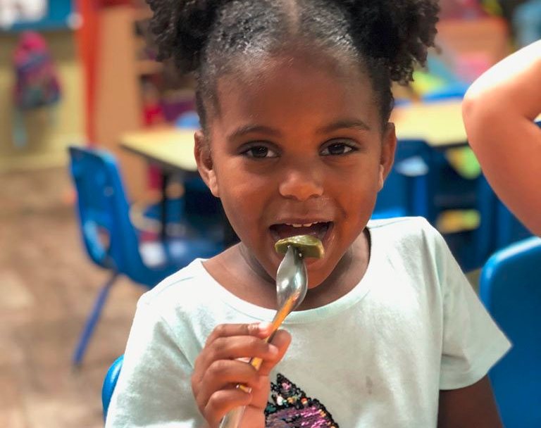 African American preschool girl eating a rice cake at a Christian Preschool & Daycare Serving Loganville, GA