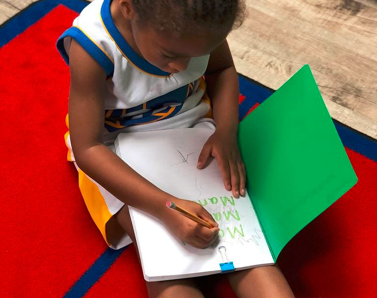 An African american preschool kid writing name on a notebook at a Christian Preschool & Daycare Serving Loganville, GA