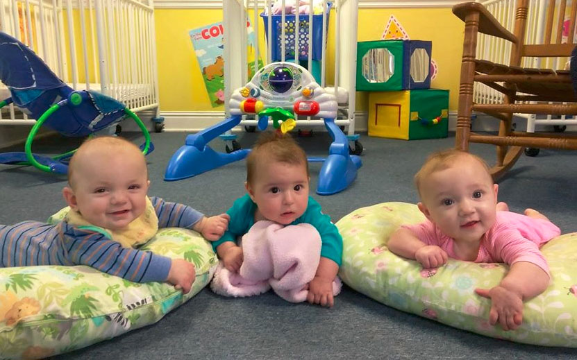 Adorable babies smiling on a pillow bed at a Christian Preschool & Daycare Serving Loganville, GA