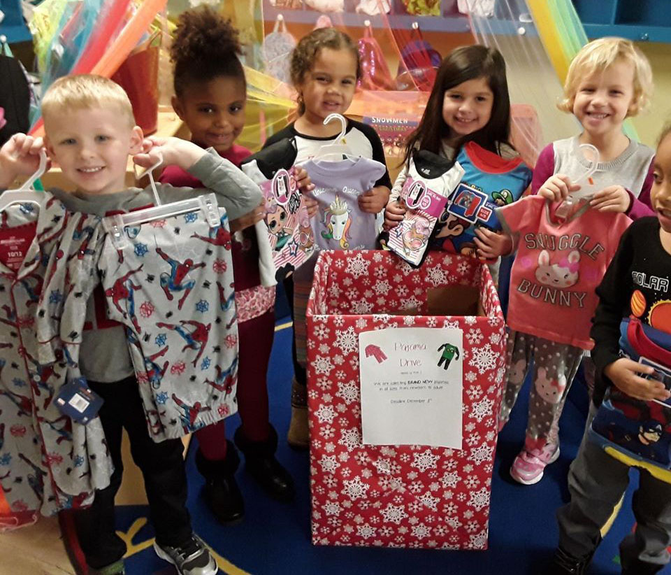 Group of diverse kids showing a new purchased clothes to be donated for a cause at a Christian Preschool & Daycare Serving Loganville, GA