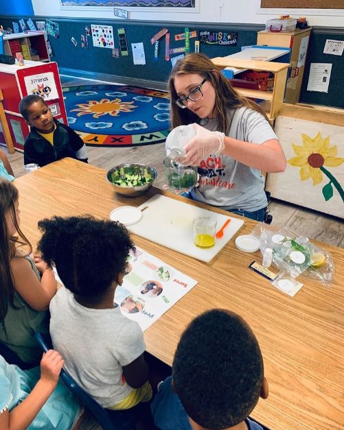 Beautiful teacher showing preschool kids how to make a healthy food with sliced vegetable at a Christian Preschool & Daycare Serving Loganville, GA