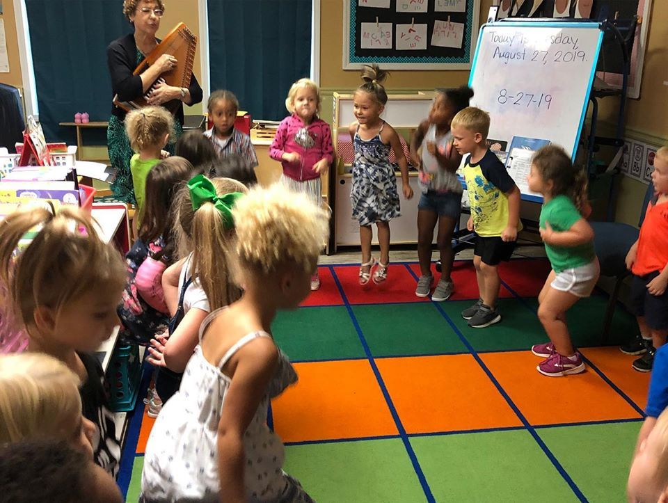 Preschool children jumping and dancing while teaching is playing a musical instrument at a Christian Preschool & Daycare Serving Loganville, GA