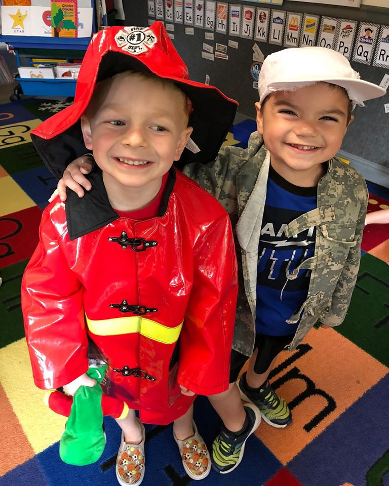 Happy little boys wearing a firefighter costume and a military costume for a school activity at a Christian Preschool & Daycare Serving Loganville, GA