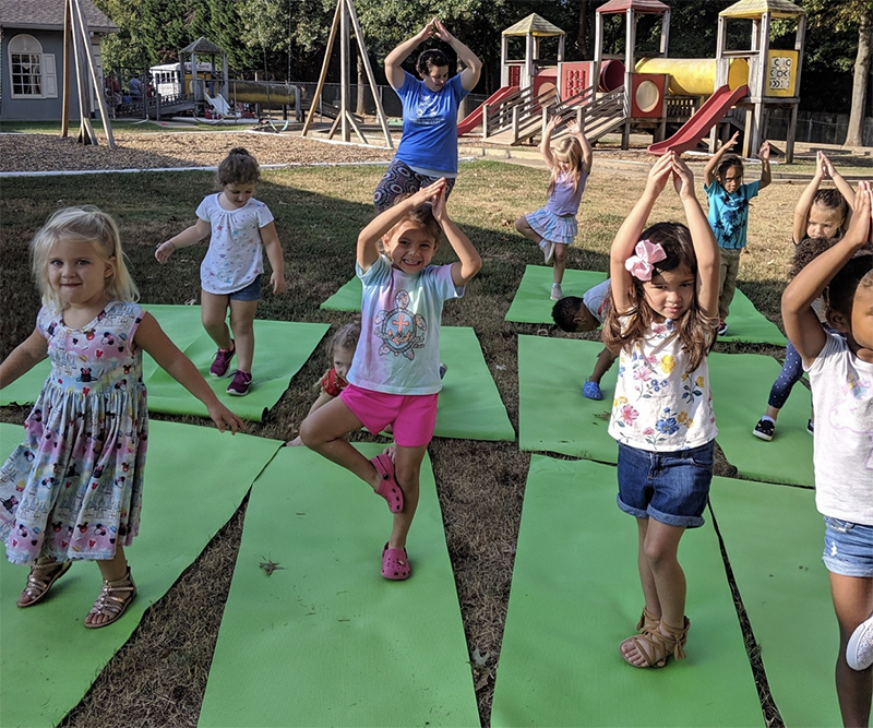 Group of kids doing yoga with their teacher on a playground at a Christian Preschool & Daycare Serving Loganville, GA