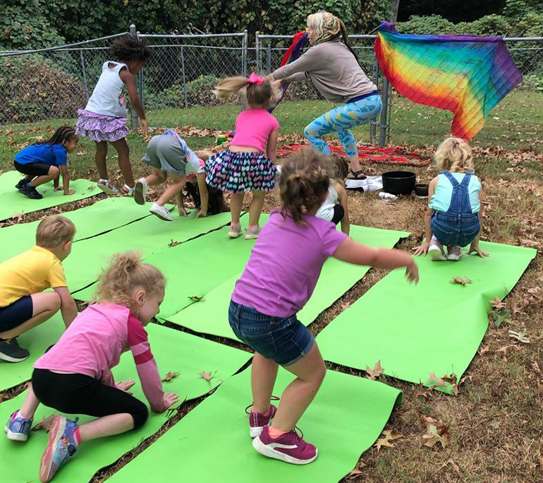 teacher and group of kids doing yoga at a Christain Preschool & Daycare Serving Loganville, GA